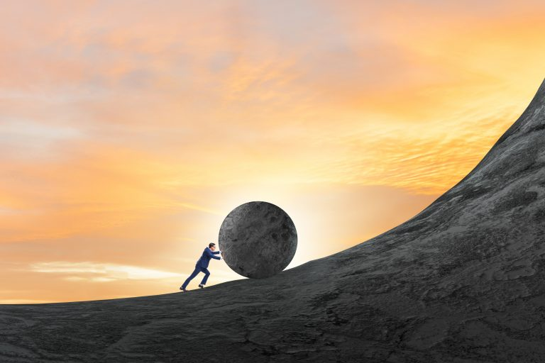 A person pushing a massive boulder up a steep hill